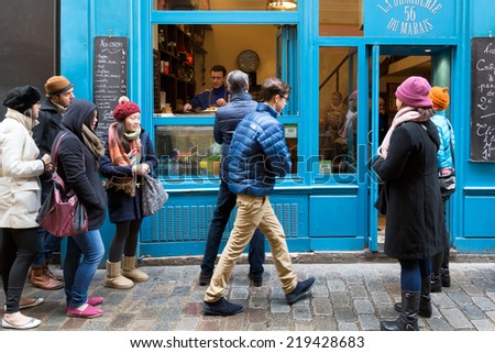 PARIS-DEC 31, 2013: People line up to buy crepes at a shop on rue des Rossiers in the Marais district, the oldest neighborhood in Paris. The sweet or savory thin pancakes are a popular snack in Paris. - stock photo