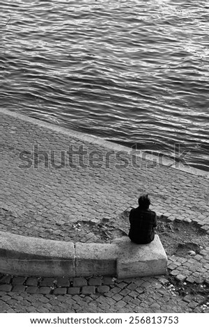 PARIS - DECEMBER 2: A middle-age lonely man takes a break at the riverside of the Seine near Pont Saint-Louis in Paris, France, on December 2, 2011. - stock photo