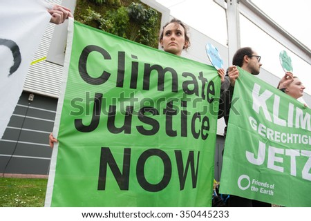 "PARIS - DECEMBER 1: Climate activists at the COP21 UN climate summit in Paris, France, stage a protest calling for ""climate justice now"", December 1, 2015. - stock photo"
