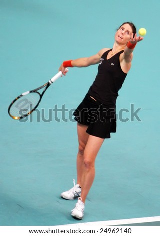 PARIS - FEBRUARY 13: French tennis player Nathalie Dechy serves during her quarter final match at Open GDF SUEZ WTA tournament, Pierre de Coubertin stadium on February 13, 2009 in Paris, France. - stock photo