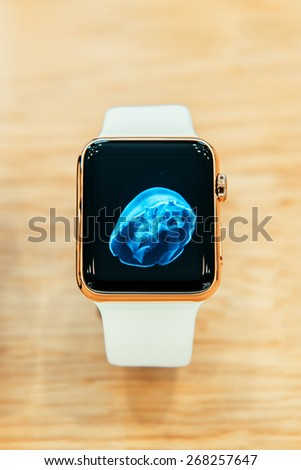 PARIS, FRANCE -  APR 10, 2015: New wearable computer Apple Watch smartwatch displaying the Edition gold collection. Apple Watch incorporates fitness tracking and health-oriented capabilities with iOS - stock photo