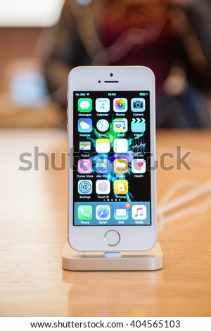 PARIS, FRANCE - APR 4, 2016: People testing new iPhone with the Apple iPhone SE in docking station during the sales launch of the latest Apple Inc. smartphone and iPad Pro at the Apple store in Paris - stock photo