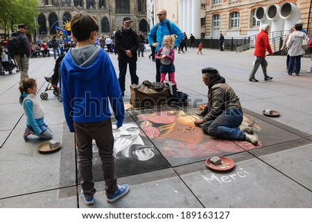 PARIS, FRANCE - APRIL 20, 2014: Artist during drawing Charlie Chaplin, Spider Man and on other funny personages on sidewalk near Centre Pompidou. Many street artists show their work near the centre. - stock photo