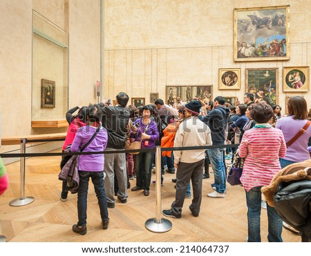 Paris, France-APRIL 14, 2013: Group of tourists gathered around the Mona Lisa in the Louvre Museum - stock photo