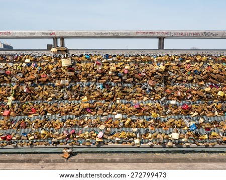 PARIS, FRANCE - APRIL 8, 2015: Padlocks on Pont des Arts. The bridge is a favourite spot for couples who attach a padlock to the railing and throw the key into the river promising eternal love. - stock photo