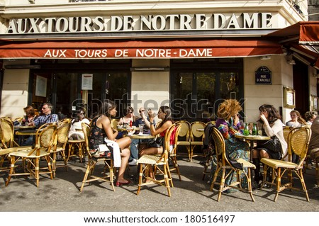 "PARIS, FRANCE - APRIL 17 : People chatting over drinks enjoing first spring sun in the cafe ""Aux Tours de Notre Dame"" near Notre-Dame cathedral on April 17th, 2013 in Paris, France - stock photo"