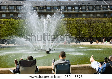 PARIS, FRANCE - APRIL 21, 2013: People relaxing around a fountain in Palais Royal garden. Palais-Royal houses the Council of State, the Constitutional Council, and the Ministry of Culture of France. - stock photo