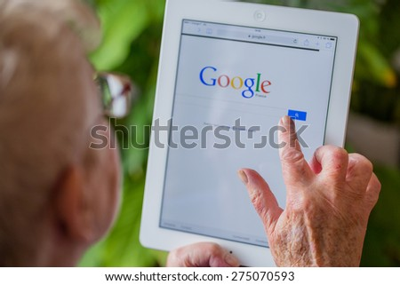 Paris, France - April 27, 2015: Senior woman using tablet with Google search home page on a ipad screen - stock photo