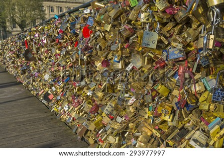 PARIS, FRANCE - APRIL 9, 2014: Too many locks of love on the railing of a bridge. Pedestrian Arts bridge over the Seine in Paris. - stock photo