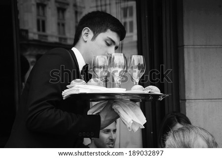 PARIS, FRANCE - APRIL 20, 2014 : Waiter serving customers at traditional outdoor Parisian cafe in center city. Street buildings are reflected in the glasses. - stock photo