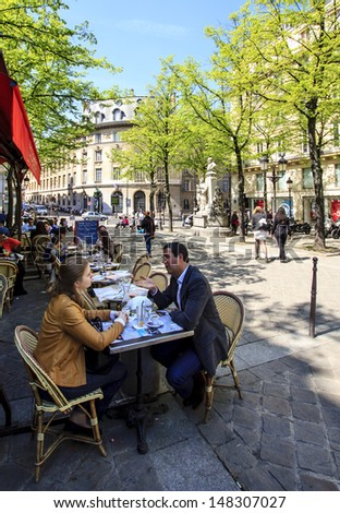 PARIS, FRANCE - APRIL 24 : Woman and man talking over a coffee in the open street cafe at the Sorbonne place on April 24th 2013 in Paris, France  - stock photo