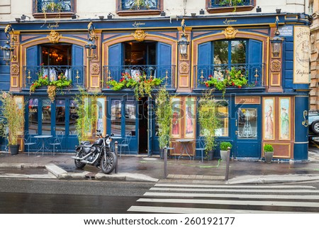 Paris, France - August 07, 2014: Black motorcycle stands parked near blue bar facade on the Quai Des Grands Augustins - stock photo