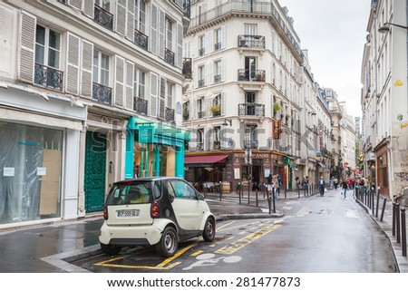 Paris, France - August 10, 2014: small white Smart car stands on the street in Paris, tourists walk on Rue St. Andre Des Arts - stock photo