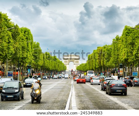 PARIS, FRANCE - AUGUST 13, 2014: The view of the Triumphal arch to the Champs-Elysees. The avenue is one of the most famous streets in the world for shopping and popular tourist attraction of Paris. - stock photo
