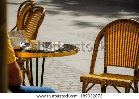 PARIS, FRANCE - AUGUST 14, 2013: Tourist sitting on terrace of Le Nemours cafe with cup of coffee, city guide (in German) and map. This popular cafe is located near Palais Royal and Comedie Francaise. - stock photo