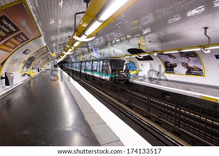 PARIS, FRANCE - CIRCA JANUARY, 2014: A train leaves a platform in the Paris metro. Traffic for the Paris metro is over 2 billion rides per year. - stock photo