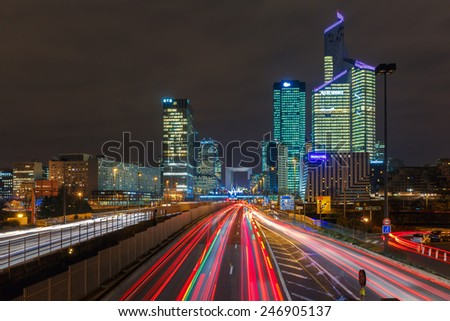 Paris, France - December 19, 2014: Night multi-lane road with skyscrapers of the La Defense. Long exposure. Defense - Parisian Manhattan, the largest business center in Europe. - stock photo
