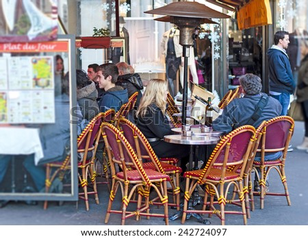 PARIS, FRANCE - DECEMBER 29 : People sitting in the footpath street cafe in winter under a heating lamp on December 29th, 2013 in Paris, France - stock photo