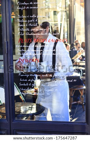 PARIS, FRANCE - DECEMBER 29 : scene in the street cafe - traditionally dressed waiter charging his tray behind the cafe's glass wall with the menu written on it on December 29th 2013 in Paris, France - stock photo