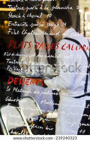 PARIS, FRANCE - DECEMBER 29 : scene in the street cafe - traditionally dressed waiters charging their trays behind the cafe's glass wall with the menu written on it on December 29th 2013  - stock photo