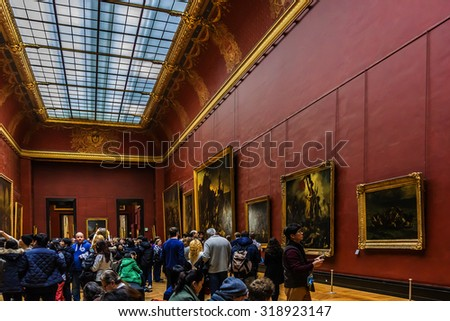 PARIS, FRANCE - DECEMBER 22, 2014: Tourists visit art gallery in Louvre Museum. Louvre Museum is one of the largest and most visited museums worldwide. - stock photo