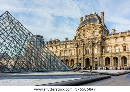 PARIS, FRANCE - DECEMBER 23, 2015: View Louvre building of Louvre Museum and Pyramid at sunset. Louvre Museum is one of the largest and most visited museums worldwide. - stock photo