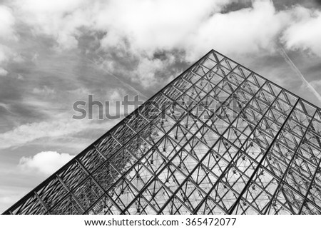PARIS, FRANCE - FEBRUARY 23, 2014: Beautiful view of the Louvre pyramid on a cloudy winter day in Paris, France, on February 23, 2014 - stock photo