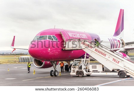 Paris , France - January 13, 2015: Airplane is near the terminal gate ready for takeoff. Crew is preparing the plane for flight. Wizzair is one of the largest low-cost airline. Airport Beauvais. - stock photo