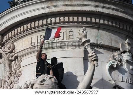 PARIS, FRANCE-JANUARY 11, 2015: Black and arab people waving the french flag during  manifestation on Republic Square in Paris against terrorism and in memory of the attack against Charlie Hebdo.  - stock photo