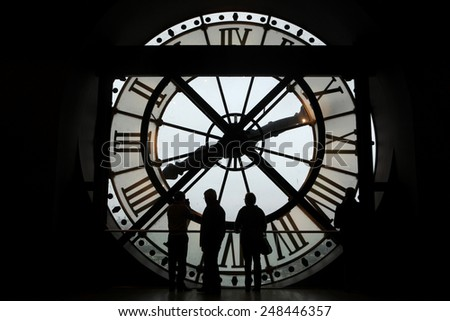 PARIS, FRANCE - JANUARY 8, 2013: Visitors observe a panoramic view thought the glass clock in the Musee d Orsay in Paris, France.  - stock photo