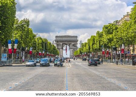 PARIS, FRANCE - JULY 14, 2014: The Champs-Elysees. Champs-Elysees - the most famous avenue of Paris has 1910m and is full of stores, cafes and restaurants. - stock photo