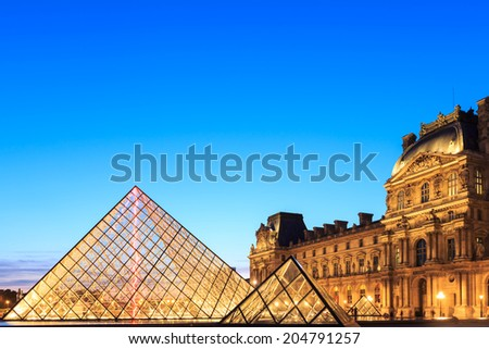 PARIS, FRANCE - JULY 19: The Louvre Pyramid at dusk during the Michelangelo Pistoletto Exhibition on July 19, 2014 in Paris. The Pyramid is the main entrance to the Louvre Museum. - stock photo