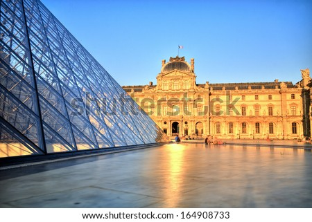PARIS, FRANCE - JULY 8: The Louvre Pyramid at dusk during the Michelangelo Pistoletto Exhibition on July 6, 2013 in Paris. Completed in 1989 and became one of the landmarks of Paris. - stock photo