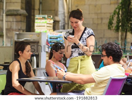 PARIS, FRANCE - JULY 28 : Young waitress taking an order from a tourist couple in an open cafe at Mouffetard street in central Paris on July 28th, 2014 in Paris, France - stock photo