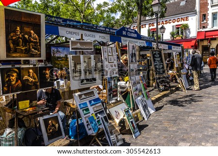 PARIS, FRANCE - JUNE 9, 2015: Artists easels and artwork set up in Place du Tertre in Montmartre. Montmartre attracted many famous modern artists including Picasso and Dali. - stock photo
