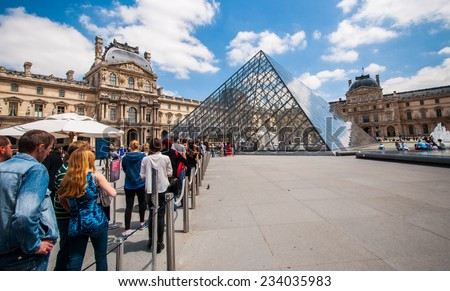 PARIS, FRANCE - JUNE 18 , 2014: Line of many Tourists in font of the Louvre's central courtyards with the Louvre pyramid and palace. The Louvre is the world's most visited museum - stock photo
