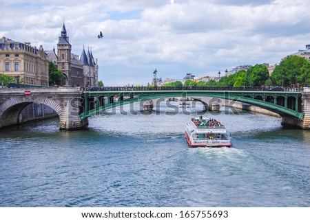 PARIS, FRANCE - JUNE 7: Seine, bridge Notre-Dame, and tourist boat, on June 7, 2009 in Paris, France. Les Halles area contains one of the largest underground modern shopping precincts in Paris. - stock photo