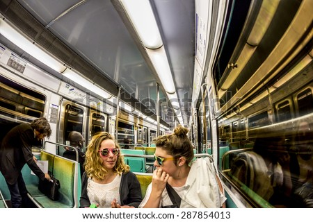 PARIS , FRANCE- JUNE 10, 2015: Tourists and locals on a subway train in Paris, France. More than 30 million people visit Paris annually. - stock photo