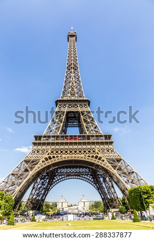 PARIS, FRANCE - JUNE 10, 2015: view of constructions of Eiffel Tower, Paris, France. People rest at champs de Mars and enjoy the spectacular view to the tower. - stock photo