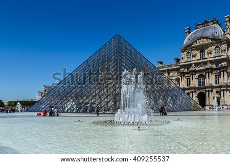 PARIS, FRANCE - JUNE 8, 2015: View of pyramid and fountain at courtyard of Louvre Museum. Louvre Museum is one of the largest and most visited museums worldwide. - stock photo