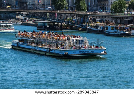 PARIS, FRANCE - JUNE 8, 2015: View of the Seine River with cruise tour boats. In Paris there are several boat tourist trips across the Seine to show tourists the sights of interest. - stock photo