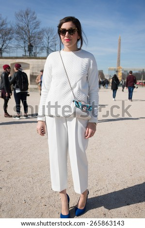 PARIS, FRANCE - MARCH 7, 2015: Stylish European woman with white dress in the Tuileries Garden. Paris Fashion Week: Ready to Wear 2015/2016 is held from March 3 to 11, 2015. - stock photo