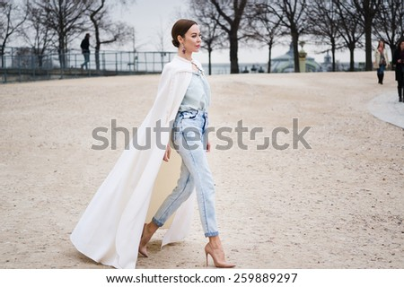 PARIS, FRANCE - MARCH 10, 2015: Stylish European woman with white mantle in the Tuileries Garden. Paris Fashion Week: Ready to Wear 2015/2016 is held from March 3 to 11, 2015. - stock photo