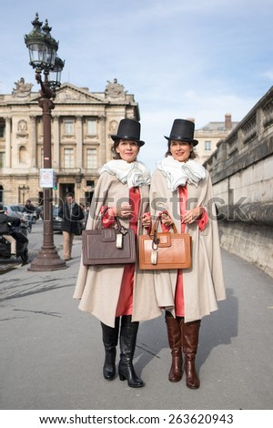 PARIS, FRANCE - MARCH 7, 2015: Stylish European women with robe in the Tuileries Garden. Paris Fashion Week: Ready to Wear 2015/2016 is held from March 3 to 11, 2015. - stock photo