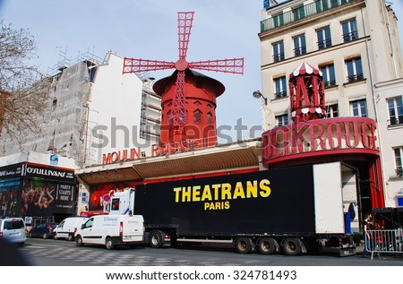 PARIS, FRANCE - MARCH 19, 2014: The famous Moulin Rouge cabaret theatre in the Boulevard de Clichy in the Pigalle district of Paris. First opened in 1899, the current building dates from 1921. - stock photo