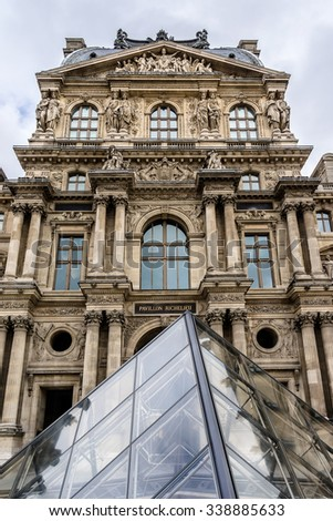 PARIS, FRANCE - MAY 8, 2014: Glass pyramid in courtyard of Louvre Palace. Louvre Museum is one of the largest and most visited museums worldwide. - stock photo