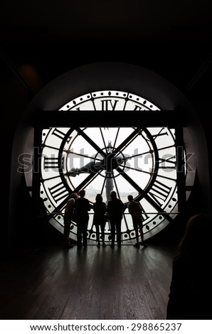 Paris, France - May 14, 2015: Silhouettes of unidentified tourists looking through the clock with roman numerals in the museum D'Orsay. - stock photo