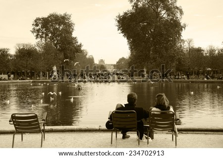 PARIS, FRANCE - NOVEMBER 22, 2014: A couple among other tourists and and Parisians rest in Tuileries garden near Louvre museum. Tuileries garden became a public park after the French Revolution. - stock photo