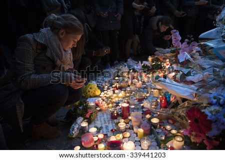 PARIS, FRANCE - NOVEMBER 15, 2015 :  A woman lights a candle in front of the theater Le Bataclan in tribute to victims of the Nov. 13, 2015 terrorist attack in Paris at the Bataclan. - stock photo
