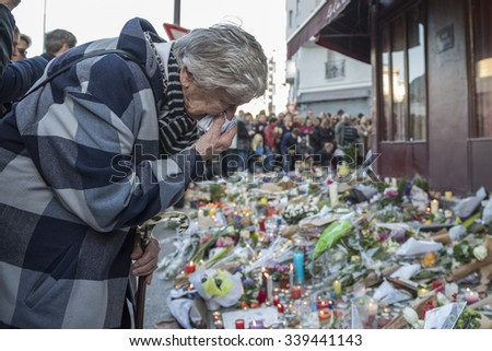 PARIS, FRANCE - NOVEMBER 15, 2015 :  An old woman very touched in front of the bar hotel Le Carillon near the theater Bataclan after the terrorist attack in Paris, November 13, 2015. - stock photo